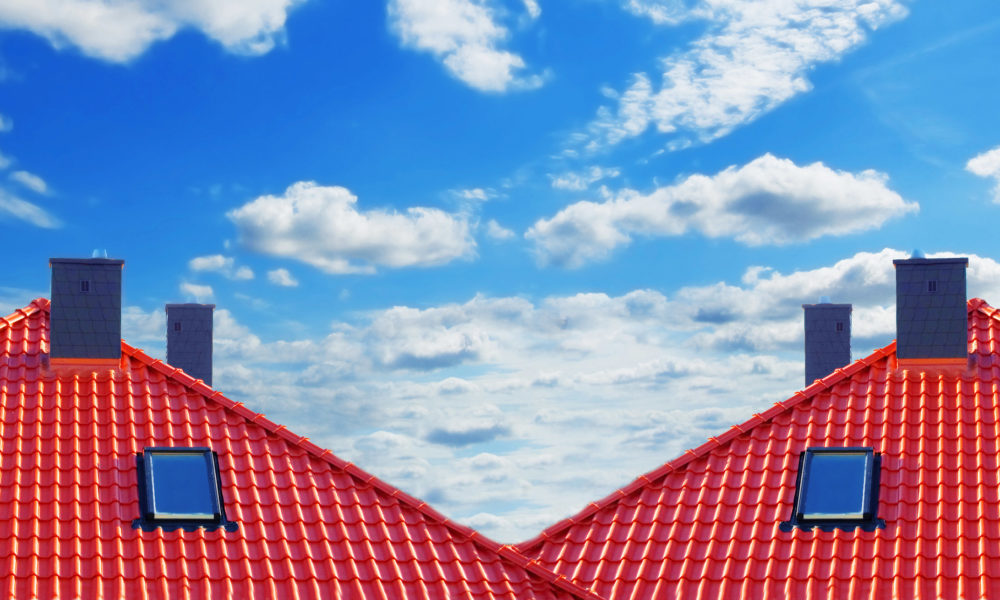 Red roof of new detached houses against blue sky.